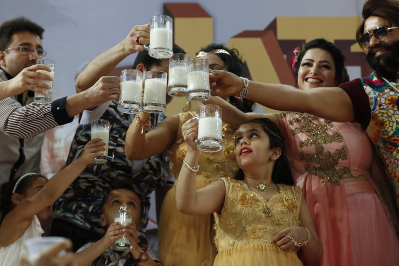 "In this May 17, 2017, file photo, Indian spiritual leader who calls himself Dr. Saint Gurmeet Singh Ram Rahim Insan, right, and others raise a toast with glasses of milk as they hold a 'Cow Milk Party' during the premiere of the movie ""Jattu Engineer"" in New Delhi, India. A judge on Monday, Aug. 28, 2017, sentenced the flamboyant and controversial Indian spiritual guru to prison on charges of raping two female followers."