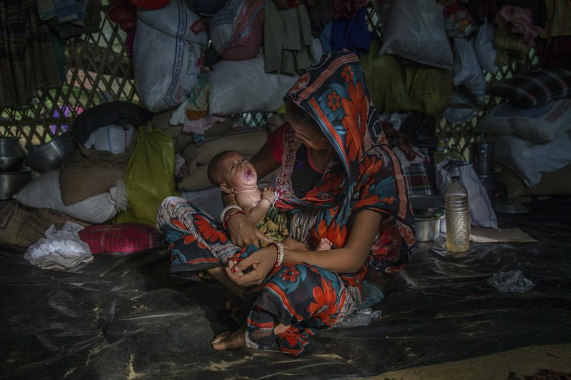 In this Monday, Sept. 25, 2017, file photo, a Hindu woman, who crossed over from Myanmar into Bangladesh, holds her baby as she sits inside a refugee camp set up for Hindu refugees near Kutupalong, Bangladesh.