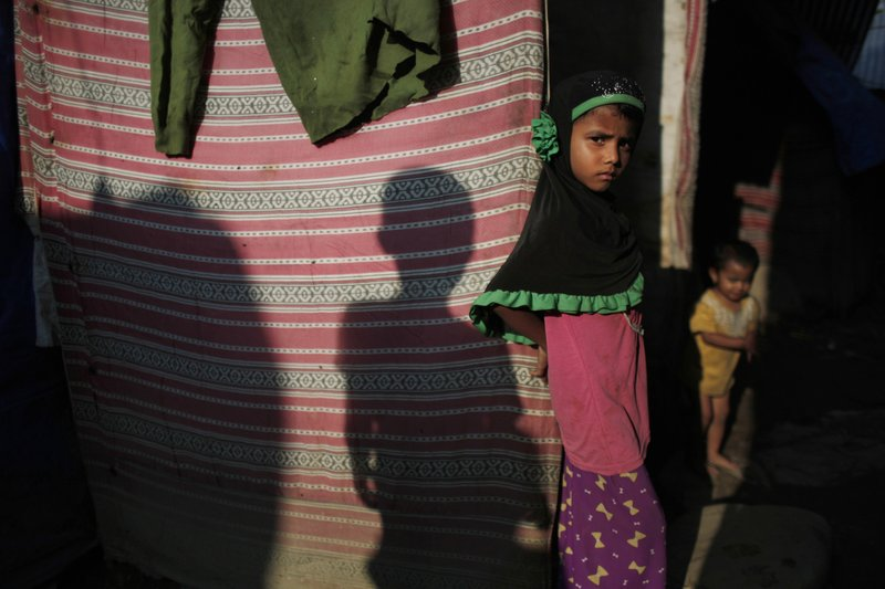 In this Sunday, Sept. 10, 2017, photo, a young Rohingya stands outside her temporary shelter at a camp in Kathmandu, Nepal. Recent violence in Myanmar has driven hundreds of thousands of Rohingya Muslims to seek refuge across the border in Bangladesh. Only about 250 Rohingya live in Nepal since anti-Muslim riots erupted in Myanmar in 2012, according to the U.N. refugee agency, which offers them education and medical support. The refugees live in a ramshackle camp carved out on a slope on the outskirts of the capital, Kathmandu. Their huts of tin, bamboo and plastic sheets are connected by narrow stone steps.