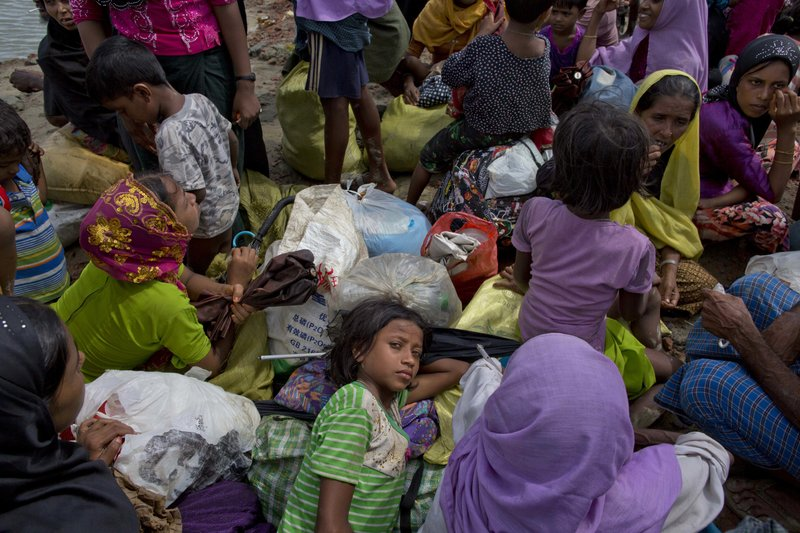 In this Friday, Sept. 29, 2017, file photo, a Rohingya Muslim girl rests on a pile of bags, as she waits with others to walk towards a camp for refugees after crossing into Bangladesh from Myanmar, in Teknaf, Bangladesh. More than a month after Myanmar's refugees began spilling across the border, the U.N. says more than half a million have arrived. The prejudice and hostility that Rohingya Muslims face in Myanmar stretch beyond the country's notoriously brutal security forces to a general population receptive to an often-virulent form of Buddhist nationalism that has seen a resurgence since the end of military rule.