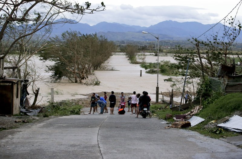 Philippines landslide: families line roads to identify bodies
