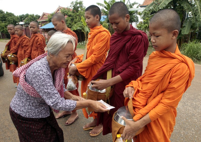 In this Friday, July 28, 2017, file photo, Buddhist monks, right, receive offerings from a devotee at Barach village in Kandal Province, northeast of Phnom Penh, Cambodia.