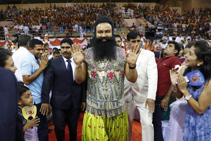 "In this Oct. 5, 2016 file photo, Indian spiritual guru who calls himself Saint Dr. Gurmeet Ram Rahim Singh Ji Insan, center, greets followers as he arrives for a press conference ahead of the release of his new movie ""MSG: The Warrior Lion Heart,"" in New Delhi, India. A judge on Monday, Aug. 28, 2017 sentenced the flamboyant and controversial Indian spiritual guru to 20 years in prison on charges of raping two female followers."
