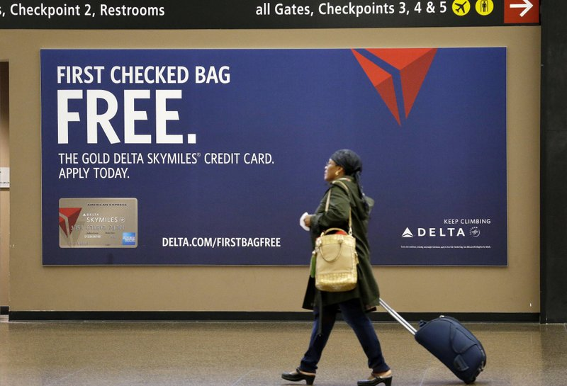 Tap your credit cards for spring break savings file in this march 24 2015 file photo a traveler walks past a sign advertising a delta air lines credit card at seattle tacoma international airport in reheart Image collections