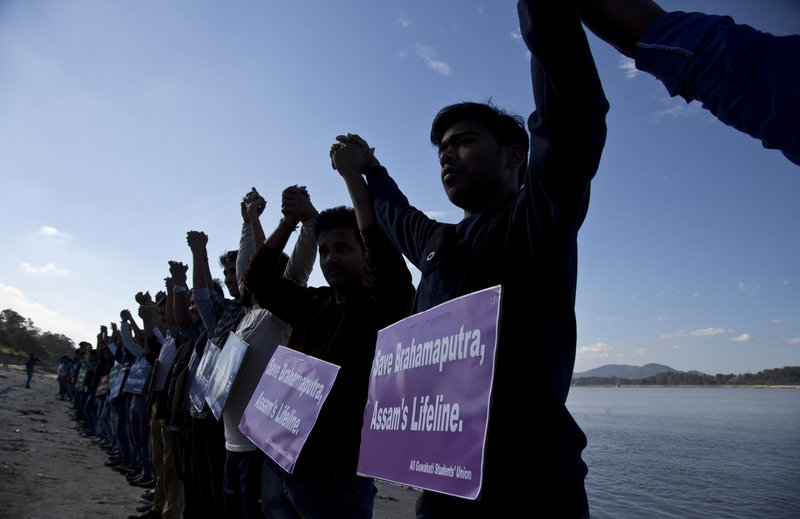 In this Monday, Dec.11, 2017 photo, students from India's northeastern Assam state hold hands by the Brahmaputra river during a protest against the contamination of the river in Gauhati, India. Officials in India's northeast are complaining that Chinese construction activity on the upper reaches of one of the largest rivers that flows into India are likely turning the waters downstream turbid and unfit for human consumption.