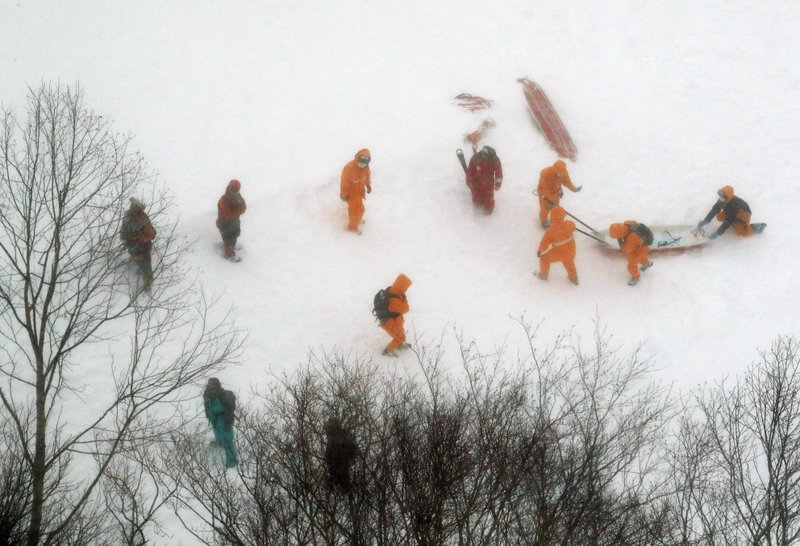 Firefighters make rescue operation at a ski resort following an avalanche in Nasu, Tochigi prefecture, Monday, March 27, 2017. Several high school students are feared dead after being caught in an avalanche Monday during a mountain climbing outing at a ski resort.