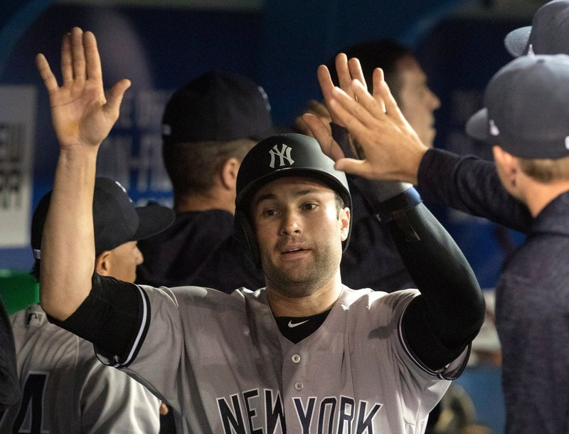 New York Yankees Neil Walker met by team mates in the dugout after scoring against the Toronto Blue Jays in the sixth inning.