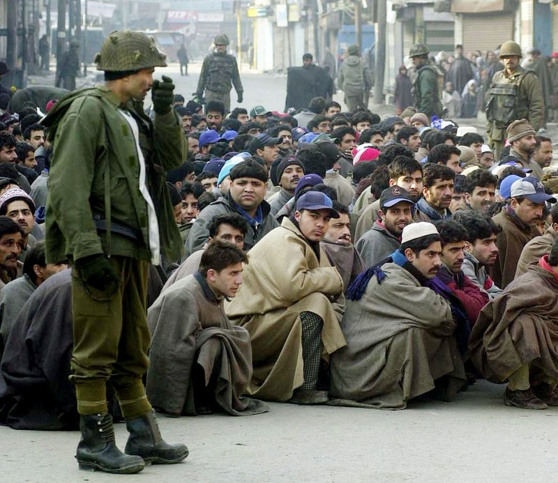 In this Jan. 23, 2002 file photo, an Indian Border Security Force soldier stands guard as Kashmiri Muslims sit on the roadside during a cordon and search operation, to flush out any possible hidden separatist militants, in Srinagar, India. No issue has bedeviled India-Pakistan relations like the disputed Himalayan region of Kashmir. As the 70th anniversary of India-Pakistan Partition comes up next week, relations between the two nations are as broken as ever.