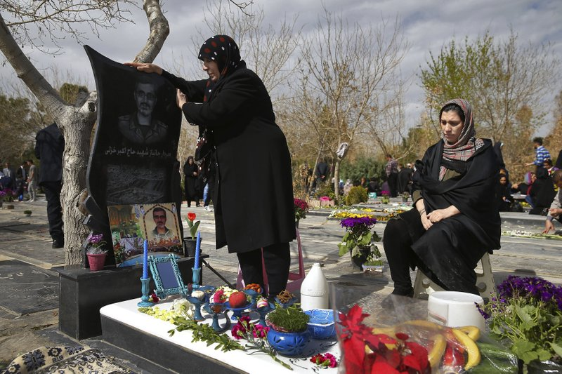 "Two Iranian women pray at the graves of soldiers who were killed during 1980-88 Iran-Iraq war, at the Behesht-e-Zahra cemetery just outside Tehran, Iran, Monday, March 20, 2017, on the eve of the Iranian New Year, or Nowruz. Nowruz which means ""New Day"" in Persian, marks the first day of spring and the beginning of the year on the Iranian calendar, which occurs exactly on the Spring Equinox."