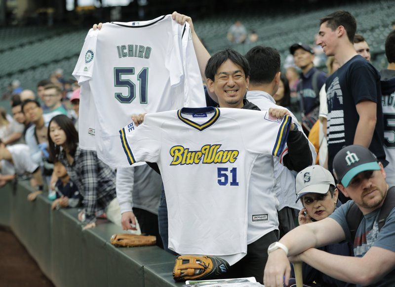 21f3f393933 Fans hold Ichiro Suzuki jerseys from the Seattle Mariners and Orix BlueWave  before a baseball game between the Mariners and the Oakland Athletics