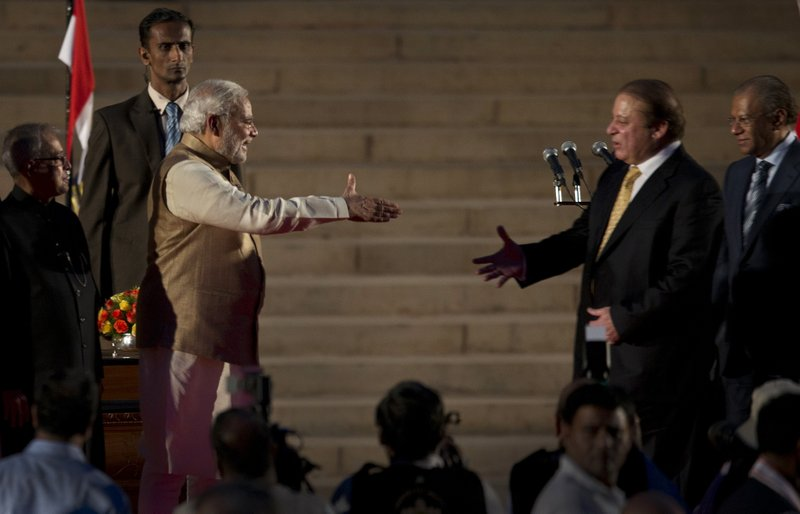 In this May 26, 2014, file photo, India's Prime Minister Narendra Modi, left, prepares to shake hands with his Pakistani counterpart Nawaz Sharif, as Mauritius Prime Minister Navinchandra Ramgoolam, right and Indian President Pranab Mukherjee, left watch during Modi's inauguration in New Delhi, India. Modi took the oath of office as India's new prime minister at the sprawling presidential palace on May 26, a moment made more historic by the presence of the leader of arch-rival Pakistan.