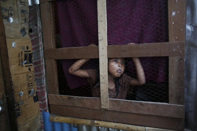 In this Sunday, Sept. 10, 2017, photo, a Rohingya girl peeps out from her temporary shelter at a camp in Kathmandu, Nepal. Recent violence in Myanmar has driven hundreds of thousands of Rohingya Muslims to seek refuge across the border in Bangladesh. Only about 250 Rohingya live in Nepal since anti-Muslim riots erupted in Myanmar in 2012, according to the U.N. refugee agency, which offers them education and medical support. The refugees live in a ramshackle camp carved out on a slope on the outskirts of the capital, Kathmandu. Their huts of tin, bamboo and plastic sheets are connected by narrow stone steps.