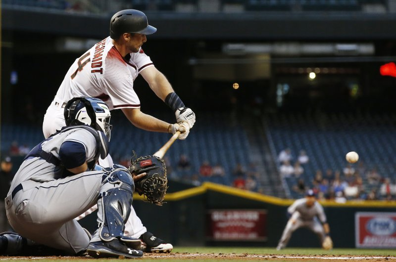 Arizona Diamondbacks' Paul Goldschmidt, top, reaches out with his bat before connecting on a run-scoring single as San Diego Padres' Austin Hedges, bottom, watches during the first inning of a baseball game, Wednesday, April 26, 2017, in Phoenix. (AP Photo/Ross D. Franklin)