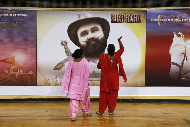 "In this Oct. 5, 2016, file photo, devotees of Indian spiritual guru, who calls himself Dr. Saint Gurmeet Singh Ram Rahim Insan, stand near a poster of his film ""MSG: The Warrior Lion Heart,"" in New Delhi, India. A judge on Monday, Aug.28, 2017, sentenced the popular and flamboyant Indian spiritual guru to prison on charges of raping two female followers."