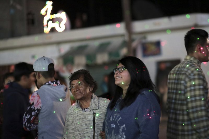 """In this Dec. 23, 2016 photo, Tamara Alcala Dominguez and her grandmother Petra Bello Suarez attend a holiday party in their home town of Molcaxac, Puebla, Mexico, during Alcala's first return home since she left Mexico for the U.S. as a toddler. The trip may have been either a last opportunity to see her grandmother, or a chance to reacquaint herself with her native land in case she winds up deported. """"It brings a lot of peace of mind to know that I was able to interact with her at least once,"""" she said, """"before whatever happens in the future."""" (AP Photo/Pablo Spencer)"""