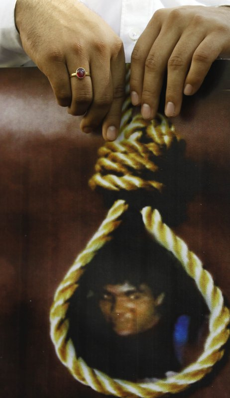 In this Nov. 21, 2012, file photo, an activist of India's main opposition Bharatiya Janata Party (BJP) holds a portrait of Mohammed Ajmal Kasab with a noose around his neck during celebrations of his execution, in Mumbai, India. India executed Kasab, the lone surviving gunman from the 2008 Mumbai terror attack, four years after Pakistani gunmen blazed through India's financial capital, killing 166 people and throwing relations between the nuclear-armed neighbors into a tailspin.