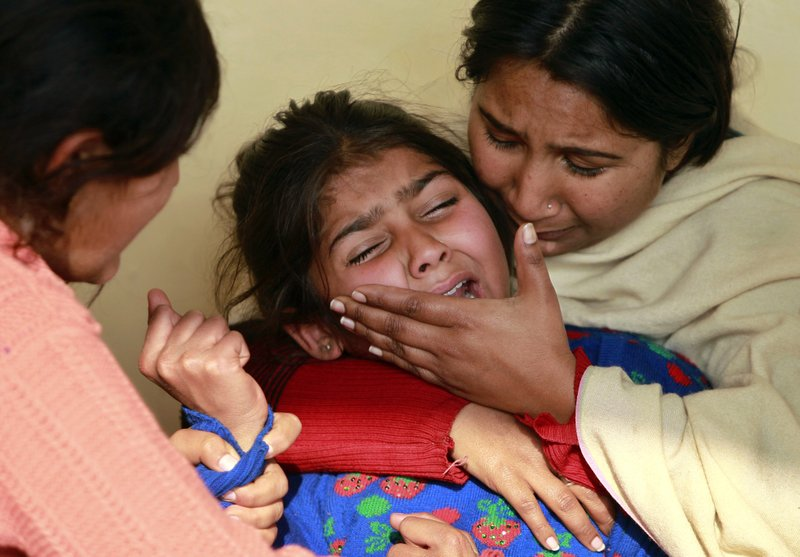 Daughter, center, of Indian civilian Gopal Dass who was killed in Pakistani firing and shelling, wails at Jhiri village in Kanachack district of Jammu and Kashmir, India, Monday, Jan.22,2018. Officials say Indian and Pakistani soldiers have again targeted each other's posts and villages along their volatile frontier in disputed Kashmir after a day's lull, killing at least one civilian.