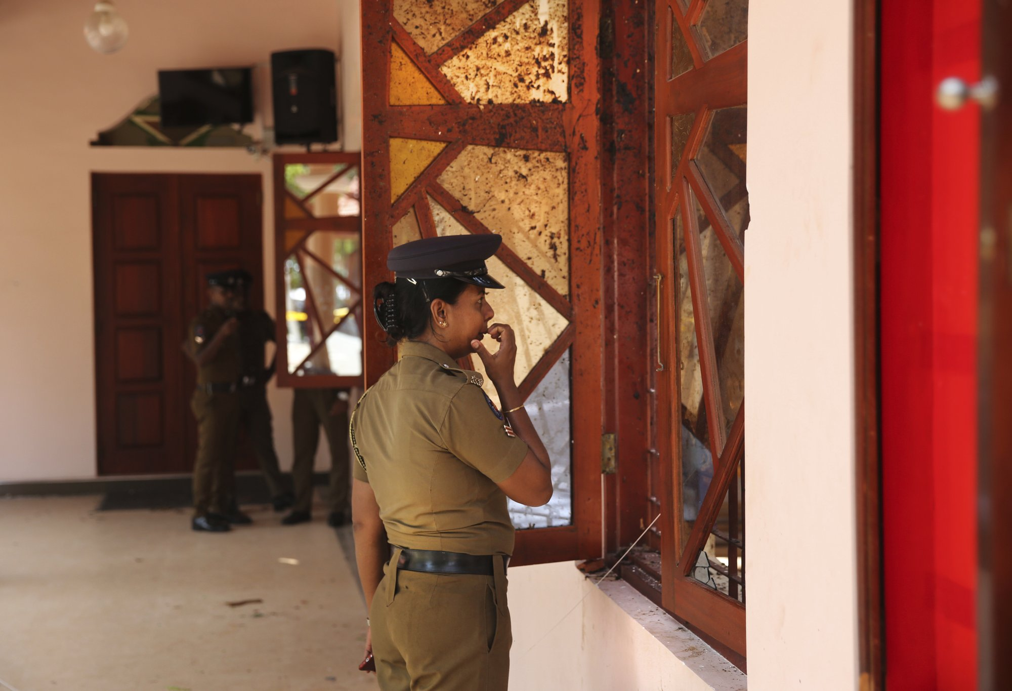 In this Thursday, April 25, 2019 photo, a Sri Lankan policewoman looks at the damage inside St. Sebastian's Church, one of the sites of Easter Sunday's bombings, in Negombo, north of Colombo, Sri Lanka. Nearly a week later, even after the cleaners have come through, the blood can still be seen clearly. The statues of Jesus and the saints are still speckled with fragments of shrapnel. The smell of death is everywhere, though the bodies are long gone. (AP Photo/Manish Swarup)