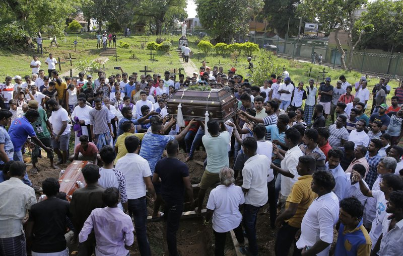 The coffins of three members of the Gomez family are carried for burial in side-by-side graves in Colombo, Sri Lanka. The family lost five loved ones in the Easter Sunday bombings. (Credit: Eranga Jayawardena/AP.)