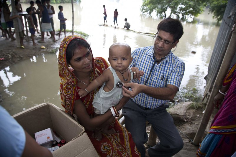 A doctor checks the child of a flood affected woman in Morigaon district, east of Gauhati, Assam, India, Tuesday, Aug. 15, 2017. Heavy monsoon rains have unleashed landslides and floods that killed dozens of people in recent days and displaced millions more across northern India, southern Nepal and Bangladesh.