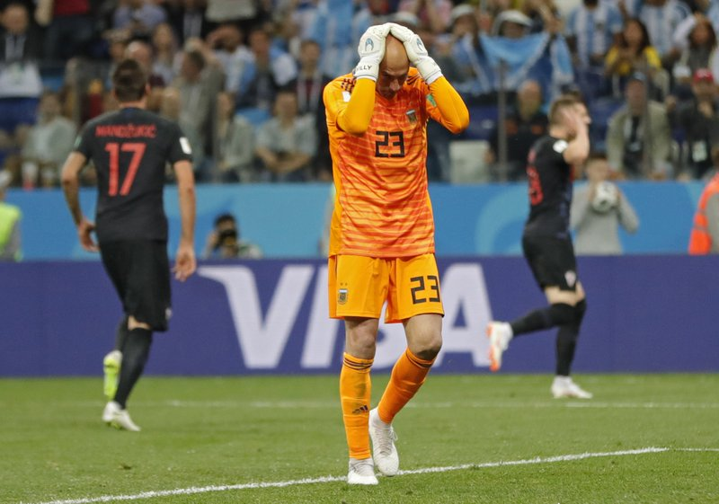 Argentina goalkeeper Wilfredo Caballero holds his head after Croatia's Ante Rebic, background right, scored the opening goal during the group D match between Argentina and Croatia at the 2018 soccer World Cup in Nizhny Novgorod Stadium in Nizhny Novgorod, Russia, Thursday, June 21, 2018.