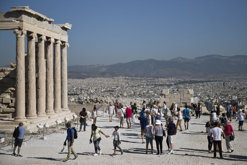 Tourist Walk Past The 5th Century BC Erechtheion Temple On The Ancient  Acropolis Hill, With The City Of Athens In The Background, On Friday ,  Sept. 1, 2017.