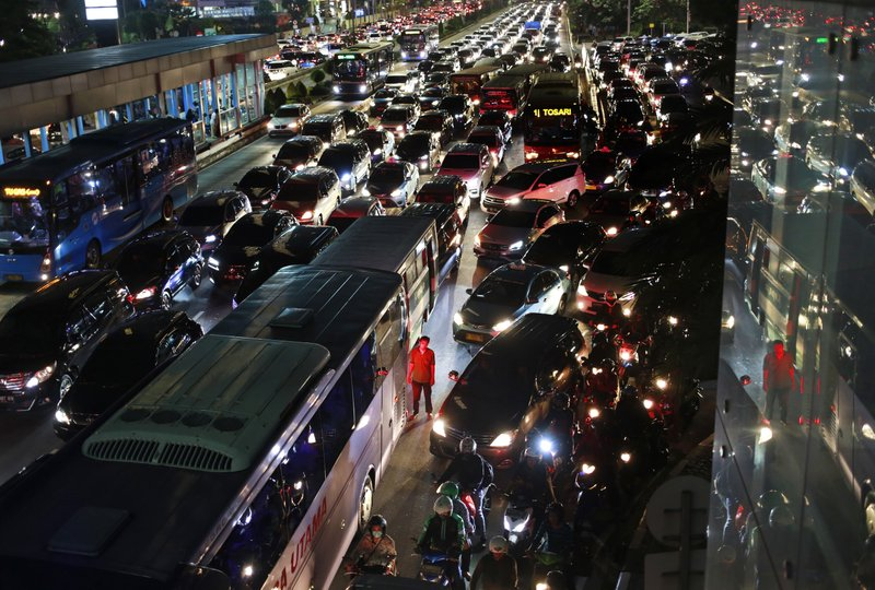 In this Friday, May 19, 2017, photo, a city bus crew member stands next to his bus as he is illuminated red by the tail lights of other vehicles in rush hour traffic in Jakarta, Indonesia.