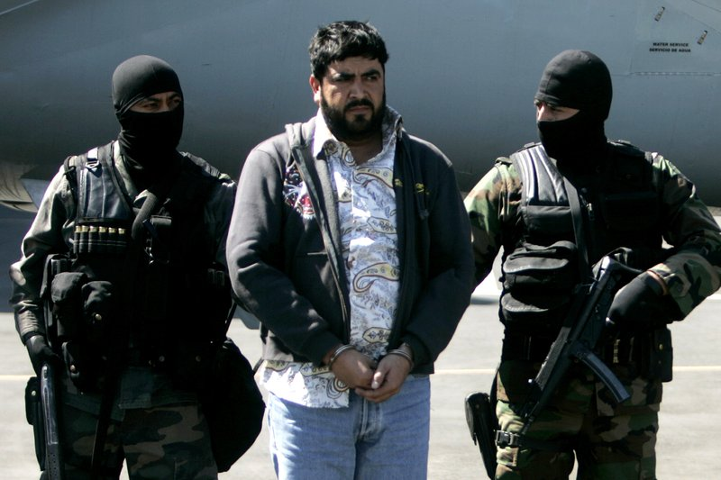 "In this Jan. 21, 2008, file photo, Mexican federal police officers escort Alfredo Beltran Leyva, known as ""El Mochomo, upon his arrival at the Mexico City's airport. Beltran Leyva, 46, was sentenced to life in prison on April 5, 2017, after pleading guilty in February to charges his multibillion-dollar operation smuggled tons of cocaine and methamphetamine into the United States."
