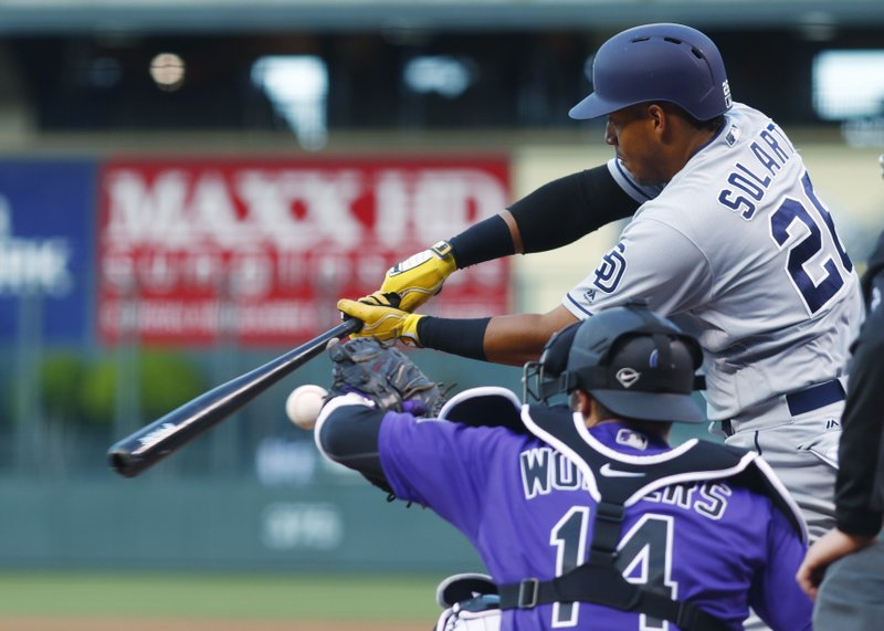 San Diego Padres' Yangervis Solarte, back, swings as Colorado Rockies catcher Tony Wolters fields a pitch in the first inning of a baseball game, Monday, April 10, 2017, in Denver. (AP Photo/David Zalubowski)