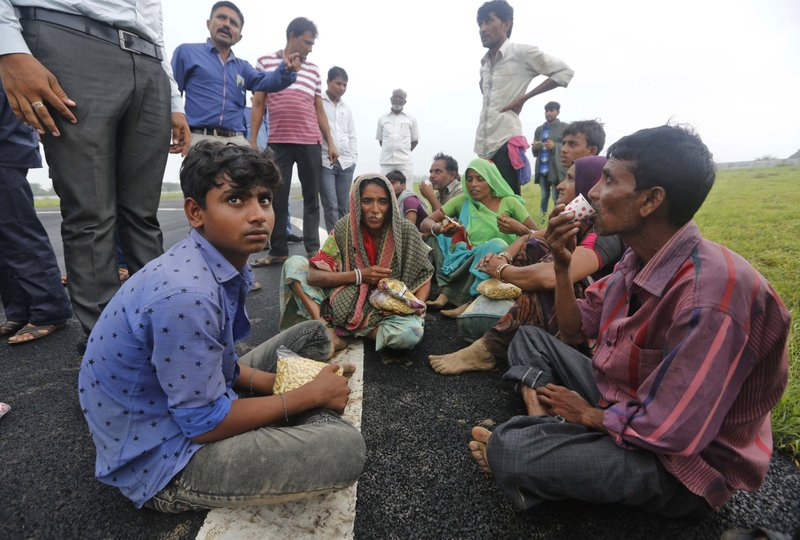 Indian flood victims who were air lifted in an air force helicopter sit at an airport in Deesa, Gujarat, India, Wednesday, July 26, 2017. At least 29 people have died in the state of Gujarat amid torrential rains. This week's deaths have taken the toll the state to 83 since the start of the monsoon season which runs from June through September.