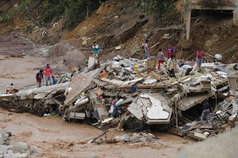 "People walk over the debris of a collapsed building in Mocoa, Colombia, Sunday, April 2, 2017. Colombia's President Juan Manuel Santos, who has declared Mocoa a disaster area, said that at least 207 were killed but that the death toll was changing ""every moment."" Authorities said another 200 people, many of them children, were injured and just as many were unaccounted for amid the destruction."