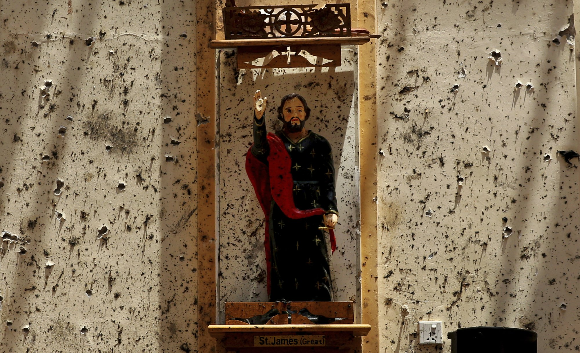 In this Thursday, April 25, 2019 photo, a statue of St. James stands on a wall speckled with fragments of shrapnel at St. Sebastian's Church, where a suicide bomber blew himself up in Negombo, north of Colombo, Sri Lanka. Nearly a week later, the smell of death is everywhere, though the bodies are long gone. Yet somehow, there's a beauty to St. Sebastian's, a neighborhood church in a Catholic enclave north of Sri Lanka's capital. You can see the beauty in the broken stained-glass windows. It's there as the sun shines through the roof's gaping holes. It's there in the little statues that refused to fall over, and despite the swarms of police and soldiers who seem to be everywhere now in the streets of the seaside town of Negombo. (AP Photo/Manish Swarup)