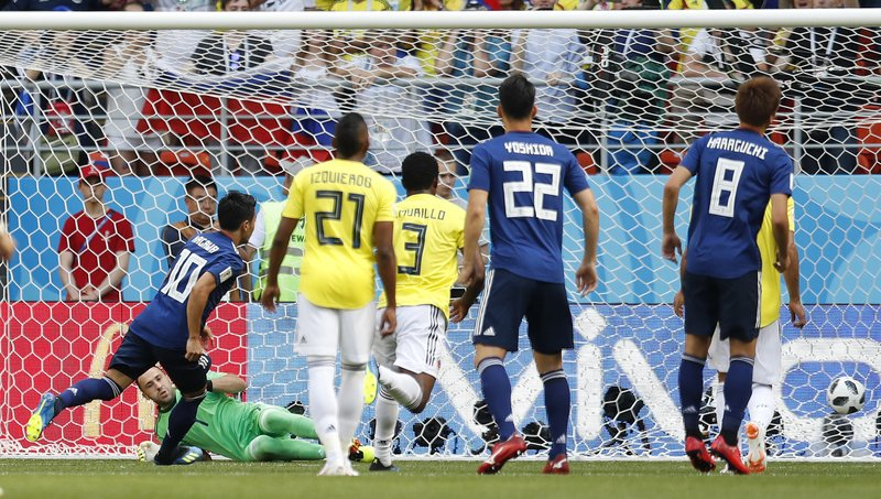 Japan's Shinji Kagawa, left, scores the opening goal during the group H match between Colombia and Japan at the 2018 soccer World Cup in the Mordavia Arena in Saransk, Russia, Tuesday, June 19, 2018.