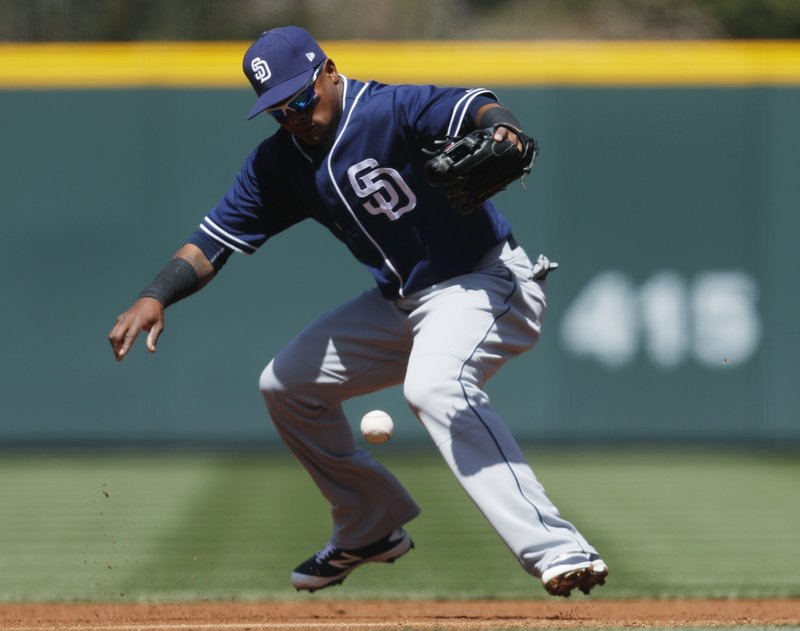 San Diego Padres' shortstop Erick Aybar juggles the ball after fielding a ground ball hit by Colorado Rockies' Carlos Gonzalez in the first inning of a baseball game Wednesday, April 12, 2017, in Denver. Akbar went on to put out Gonzalez. (AP Photo/David Zalubowski)