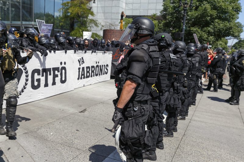 Members of Patriot Prayer gather at a rally in Portland, Ore., and are met by counter-protesting Antifa, on Saturday, Aug. 4, 2018. (AP Photo/John Rudoff)
