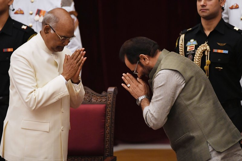 Bhartiya Janata Party (BJP) politician Mukhtar Abbas Naqvi, right, greets Indian President Ramnath Kovind after taking the oath during the swearing-in ceremony of new ministers at the Presidential Palace in New Delhi, India, Sunday, Sept.3, 2017. India Prime Minister Narendra Modi, on Sunday reshuffled some of his key minister's portfolios to refurbish his government's image, which has been dented by falling economic indicators.