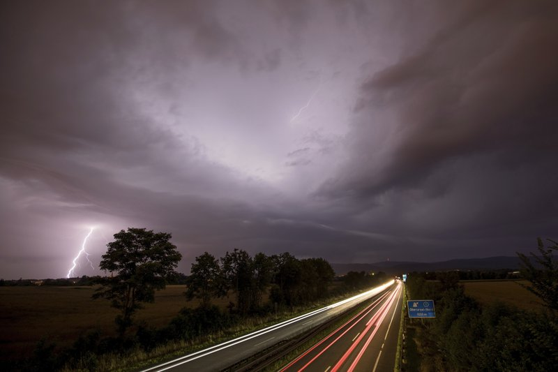 In this photo made with a long exposure, cars drive by as lightning strikes during thunderstorms in Oberursel, Germany, near Frankfurt on Saturday, July 22, 2017.