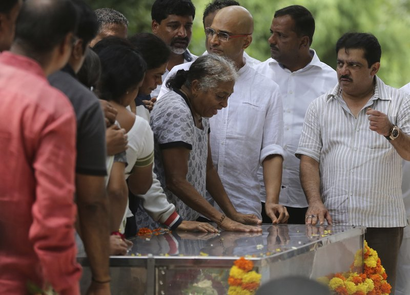 Indra Lankesh, center, mother of Indian journalist Gauri Lankesh breaks down on seeing the body of her daughter placed in a casket for public viewing in Bangalore, India, Wednesday, Sept. 6, 2017. The Indian journalist was gunned down outside her home the southern city of Bangalore — the latest in a string of deadly attacks targeting journalists or outspoken critics of religious superstition and extreme Hindu politics.