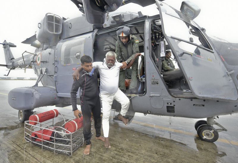 An Indian fisherman who was stranded in the Arabian Sea is escorted down from an Indian Navy helicopter after being rescued in Thiruvananthapuram, Kerala state, India, Friday, Dec.1, 2017. Dozens of fishermen were rescued from the sea which is very rough under the influence of Cyclone Ockhi.