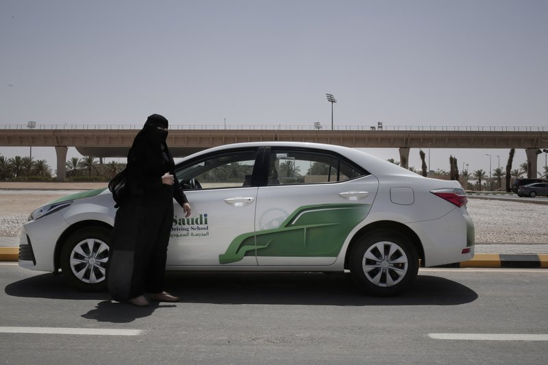 In this June 23, 2018 photo, 27-year old driving instructor Mabkhoutah al-Mari stands next to a test drivers car at the Saudi Driving School inside Princess Nora University in Saudi Arabia. As Saudi Arabia prepares to lift a ban on women driving, Saudi women are being pushed to the forefront of a major transformation being spearheaded by the country's Crown Prince Mohammed bin Salman. It also places women in the crosshairs of a decades-old pull-and-tug between Saudis agitating for more social openings and a majority that remains deeply conservative.