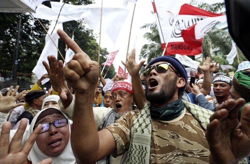 "Muslim protesters shout slogans during a protest against Jakarta's Christian Governor Basuki ""Ahok"" Tjahaja Purnama outside a court where his trial is held in Jakarta, Indonesia, Tuesday, May 9, 2017. An Indonesian court on Tuesday sentenced the minority Christian governor of Jakarta to two years in prison for blaspheming the Quran, a shock decision that undermines the country's reputation for practicing a moderate form of Islam."