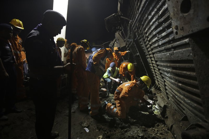 Rescuers try to retrieve the body of a victim from upturned coaches of the Kalinga-Utkal Express after an accident near Khatauli, in the northern Indian state of Uttar Pradesh, India, Sunday, Aug. 20, 2017. Six coaches of a passenger train derailed in northern India on Saturday, killing more than 20 people and injuring dozens, officials said.