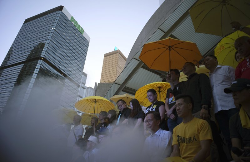 In this Thursday, Sept. 28, 2017, file photo, pro-democracy protesters holding iconic yellow umbrellas stand outside the government headquarters in Hong Kong as they release vapor which symbolized the tear gas fired by police three years ago. Protesters gathered to observe a moment of silence to mark the third anniversary of the start of the Occupy Central civil disobedience movement.