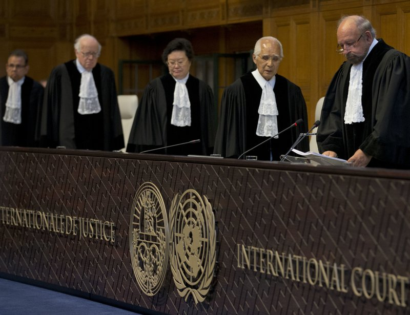 Presiding judge Ronny Abraham of France, right, enters to read the World Court's verdict in the case brought by India against Pakistan in The Hague, Netherlands, Thursday, May 18, 2017. India took Pakistan to the United Nations' highest court in an attempt to save the life of an Indian naval officer sentenced to death last month by a Pakistani military court after being convicted of espionage.