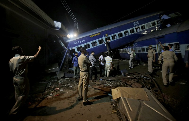 Rescuers and onlookers stand near the upturned coaches of the Kalinga-Utkal Express after an accident near Khatauli, in the northern Indian state of Uttar Pradesh, India, Sunday, Aug. 20, 2017. Six coaches of a passenger train derailed in northern India on Saturday, killing more than 20 people and injuring dozens, officials said.