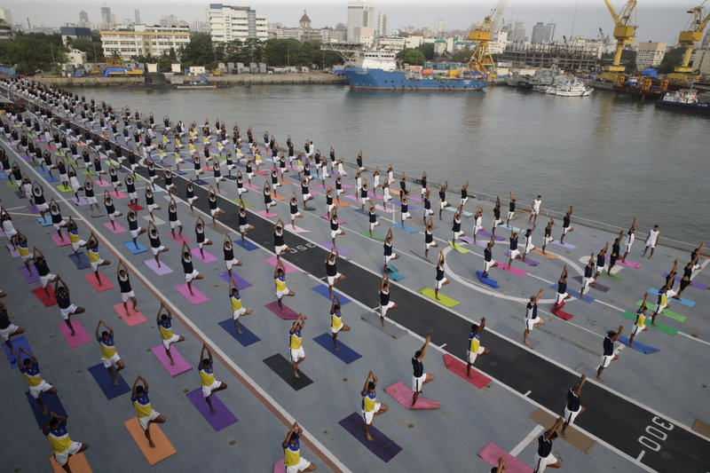 Indian defense personnel perform yoga on the deck of Indian naval aircraft carrier Viraat as they mark International Yoga Day in Mumbai, India, Thursday, June 21, 2018. Millions of yoga enthusiasts across the world Thursday took part in mass yoga events to mark International Yoga Day.