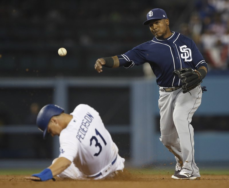 San Diego Padres' shortstop Erick Aybar, right, makes the relay over Los Angeles Dodgers' Joc Pederson in time to get Yasmani Grandal at first for a double play during the fourth inning of a baseball game in Los Angeles, Wednesday, April 5, 2017. (AP Photo/Alex Gallardo)