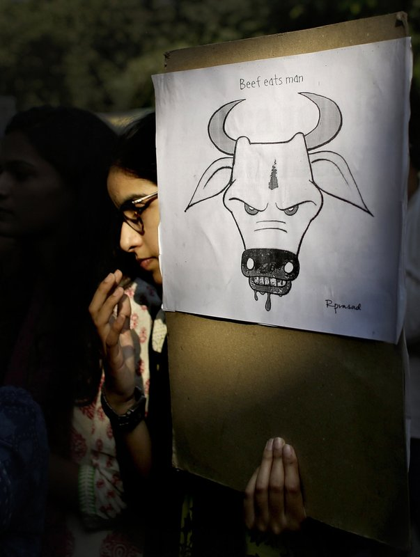 In this Oct. 2, 2015 file photo, a student activist holds a placard during a protest denouncing the killing of a 52-year-old Muslim farmer Mohammad Akhlaq by villagers upon hearing rumors that the family was eating beef, a taboo for many among India's majority Hindu population, in New Delhi, India. A Muslim man accused of transporting cows for slaughter has died after he was beaten by a mob in western India, police said Wednesday, April 5, 2017, in the latest incidence of violence by Hindu vigilante groups enraged over the treatment of animals they consider sacred.