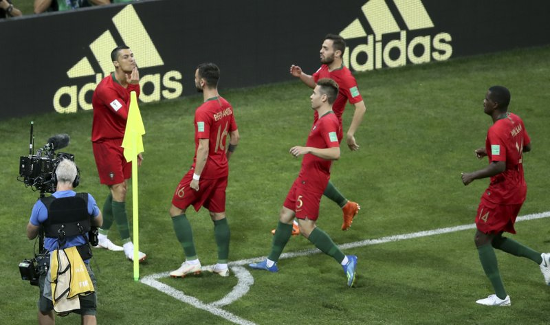 Portugal's Cristiano Ronaldo, left, celebrates after scoring the opening goal by penalty during the group B match between Portugal and Spain at the 2018 soccer World Cup in the Fisht Stadium in Sochi, Russia, Friday, June 15, 2018.