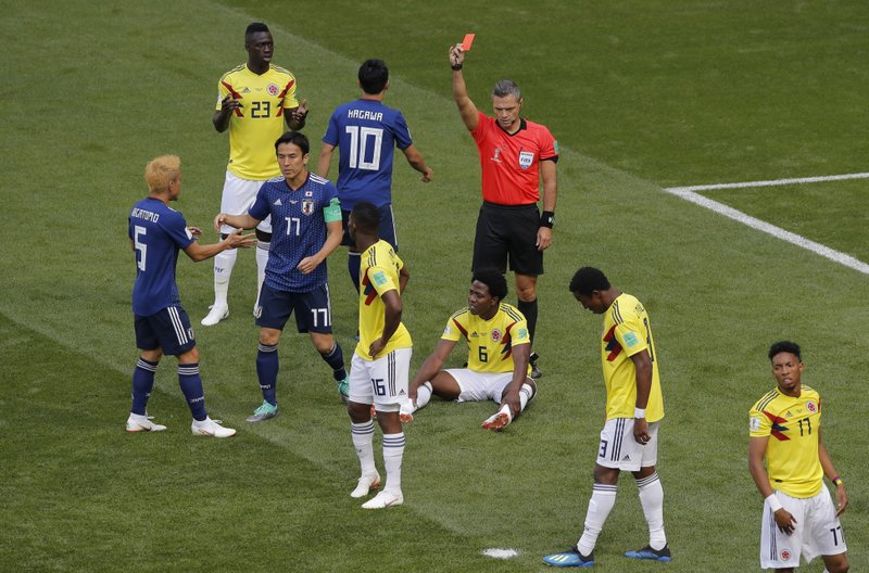 Referee Damir Skomina from Slovenia shows a red card to Colombia's Carlos Sanchez, on the ground, during the group H match between Colombia and Japan at the 2018 soccer World Cup in the Mordavia Arena in Saransk, Russia, Tuesday, June 19, 2018.